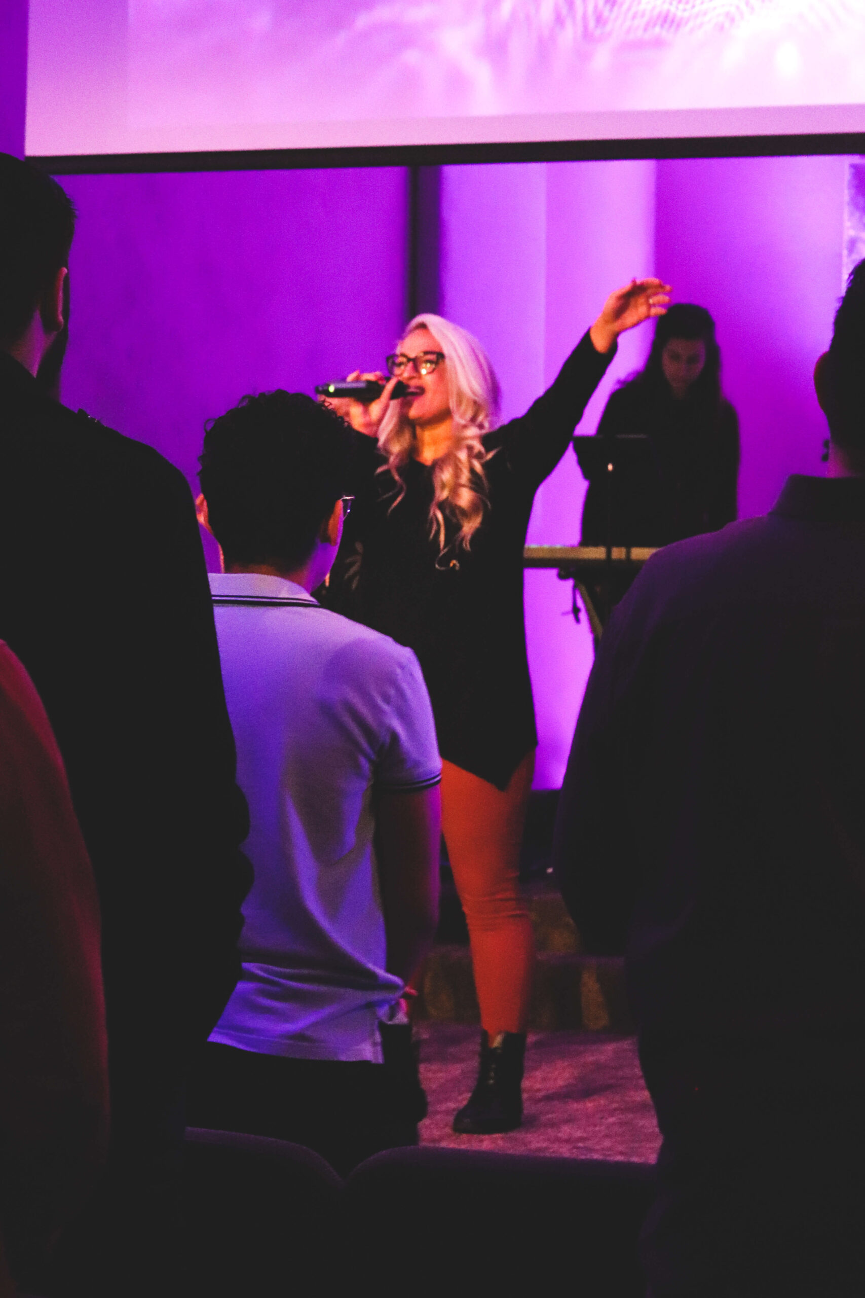 Young blonde woman leads worship with left hand raised.
